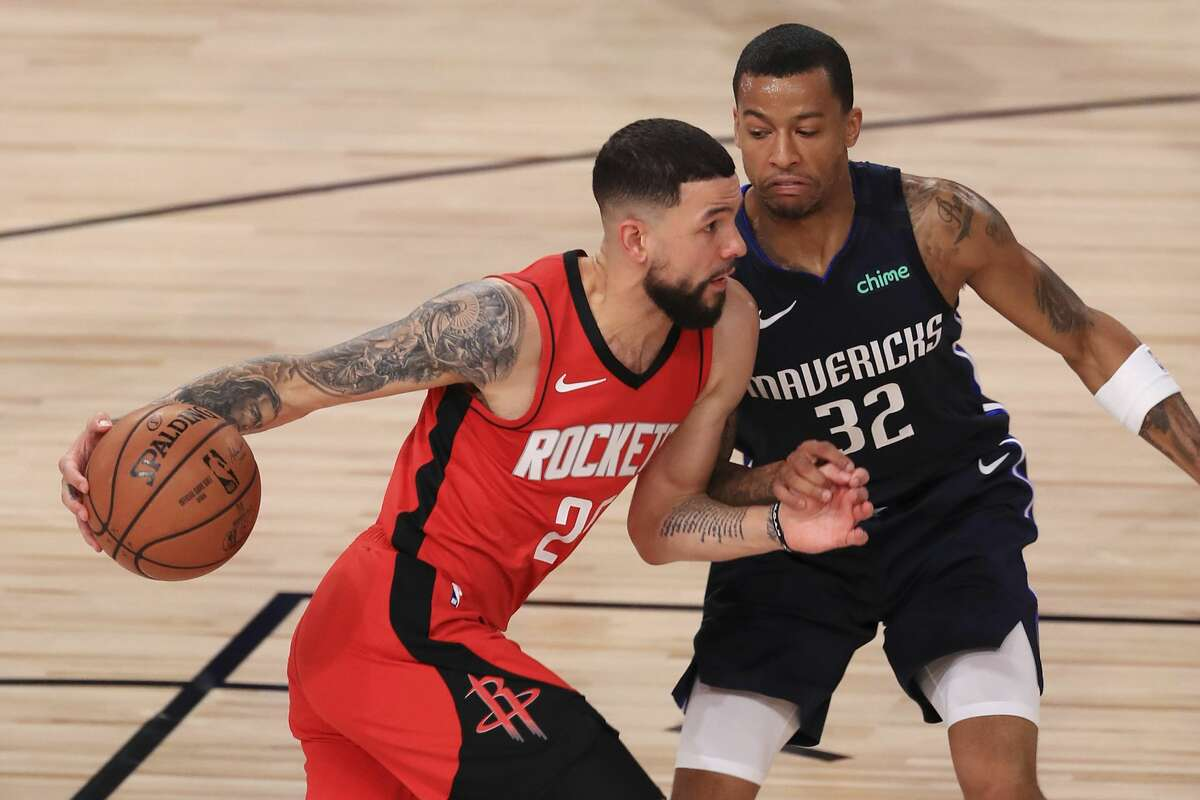 Houston Rockets' Austin Rivers, left, drives to the basket against Dallas Mavericks' Trey Burke (32) during the first half of an NBA basketball game Friday, July 31, 2020, in Lake Buena Vista, Fla. (Mike Ehrmann/Pool Photo via AP)