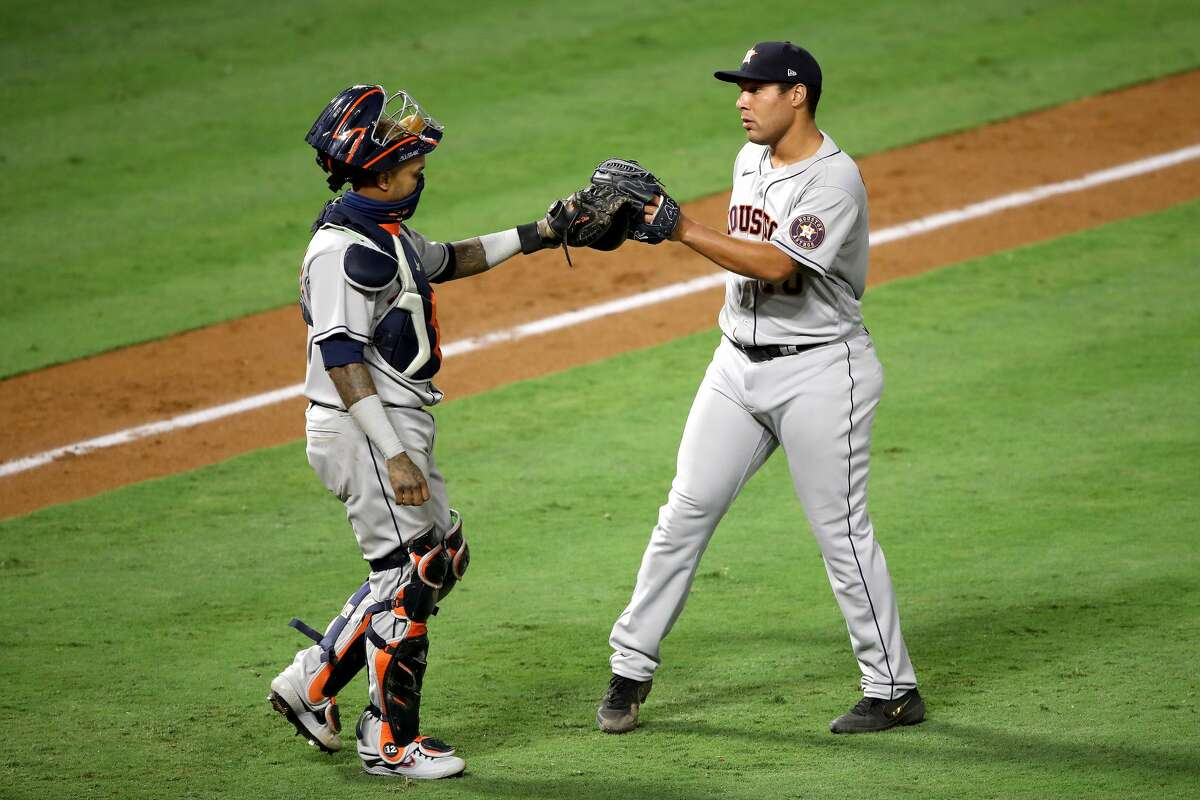 ANAHEIM, CALIFORNIA - JULY 31: Martin Maldonado #15 and Andre Scrubb #70 of the Houston Astros celebrate defeating the Los Angeles Angels 9-6 in a game at Angel Stadium of Anaheim on July 31, 2020 in Anaheim, California. (Photo by Sean M. Haffey/Getty Images)