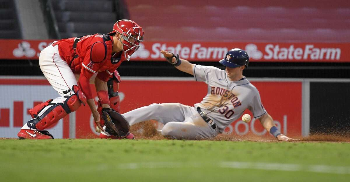 Houston Astros' Kyle Tucker, right, scores on a sacrifice fly by George Springer as Los Angeles Angels catcher Jason Castro takes a late throw during the fourth inning of a baseball game Friday, July 31, 2020, in Anaheim, Calif. (AP Photo/Mark J. Terrill)