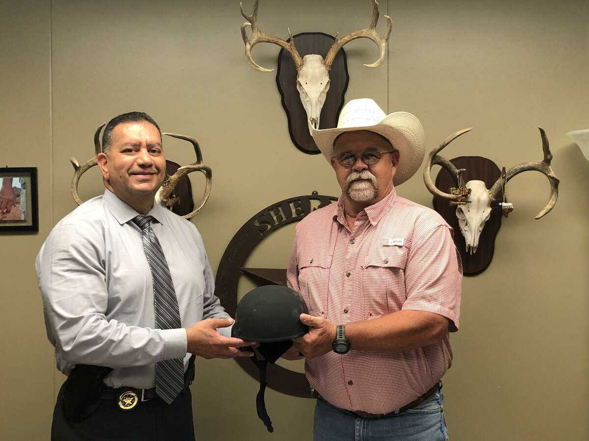 Major Jose Sanchez, a member of the Criminal Investigations Division of the Texas Department of Public Safety, is seen handing a tactical helmet to Hale County Sheriff David Cochran earlier this week. Sanchez presented the Hale County SWAT team with seven tactical helmets to help replace some of the older helmets Deputy Mark Brown's team had been using. Brown said he had heard that DPS had some helmets that were being given out and wrote a letter to request that his squad be chosen for them. Sanchez came to Plainview on Wednesday to give Cochran the helmets. Brown said that his team was need of helmets as theirs were outdated. The SWAT team consists of 10 men who are deployed on calls for things such as serving warrants and the new helmets will help protect the team members on those calls.