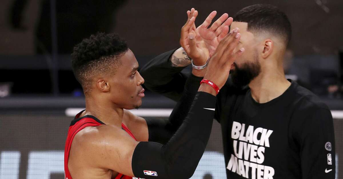 Houston Rockets Russell Westbrook, left, celebrates with teammates after defeating the Dallas Mavericks in an NBA basketball game Friday, July 31, 2020, in Lake Buena Vista, Fla. (Mike Ehrmann/Pool Photo via AP)