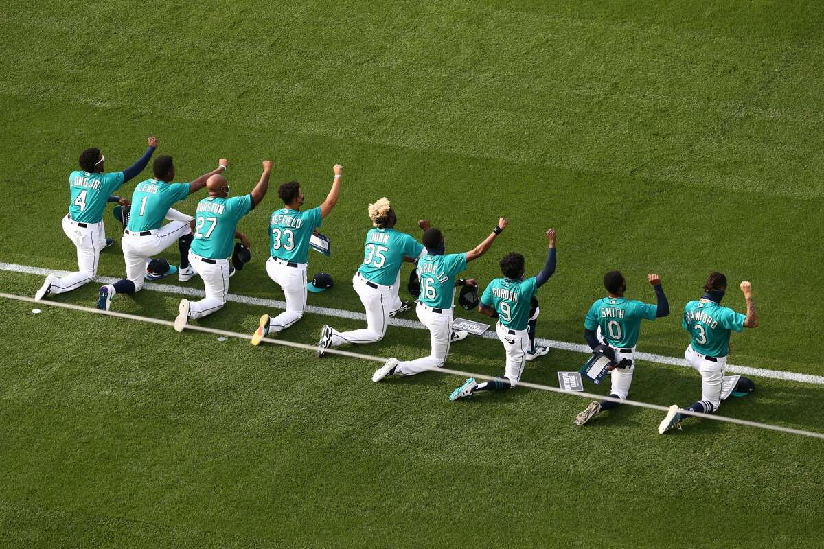 SEATTLE, WASHINGTON - JULY 31: (L-R) Shed Long Jr. #4, Kyle Lewis #1, Joe Thurston #27, Justin Dunn #35, Carl Edwards Jr., Dee Gordon #9, Mallex Smith #0 and J.P. Crawford #3 of the Seattle Mariners take a kneel after the National Anthem prior to their Opening Day game against the Oakland Athletics at T-Mobile Park on July 31, 2020 in Seattle, Washington. (Photo by Abbie Parr/Getty Images)
