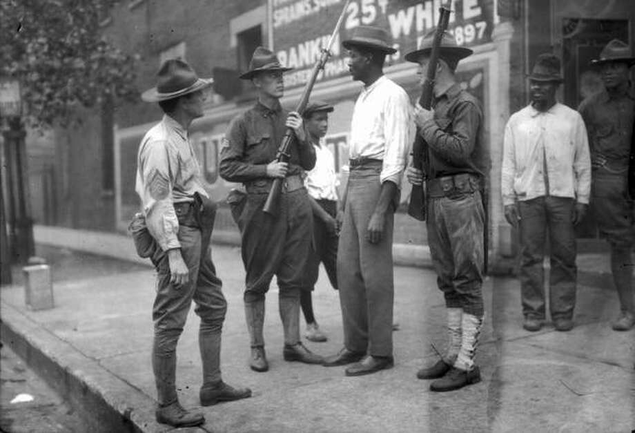 National Guardsmen, called in after three days of rioting, question a Black man in Chicago in 1919. Photo: Jun Fujita | Chicago History Museum (Getty Images)