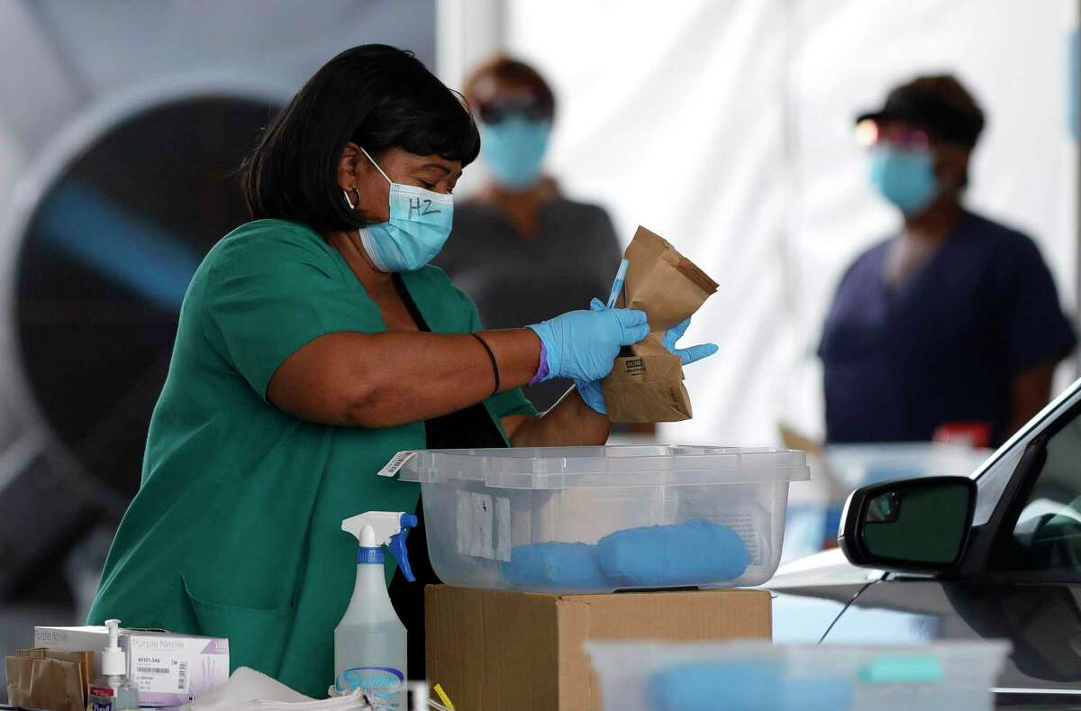 A woman gathers testing supplies for a patient to use a self-administered coronavirus test at Pridgeon Stadium, one of Harris County Public Health's eight coronavirus testing sites, Friday, July 31, 2020, in Cypress.