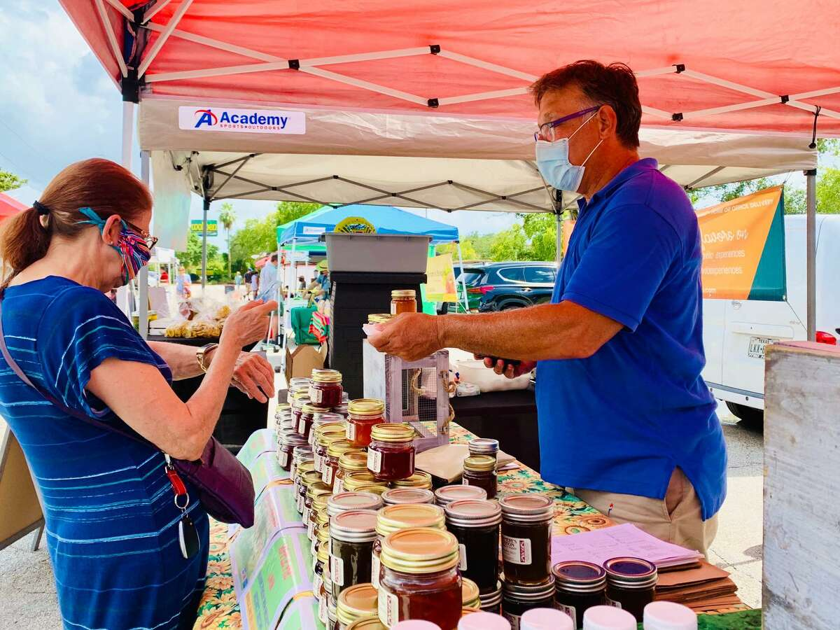 Jay Hiebert makes a sale to a customer for two glasses of jams from his company Ma-Mere's Maison at the Westchase District Farmers Market on the afternoon of July 30