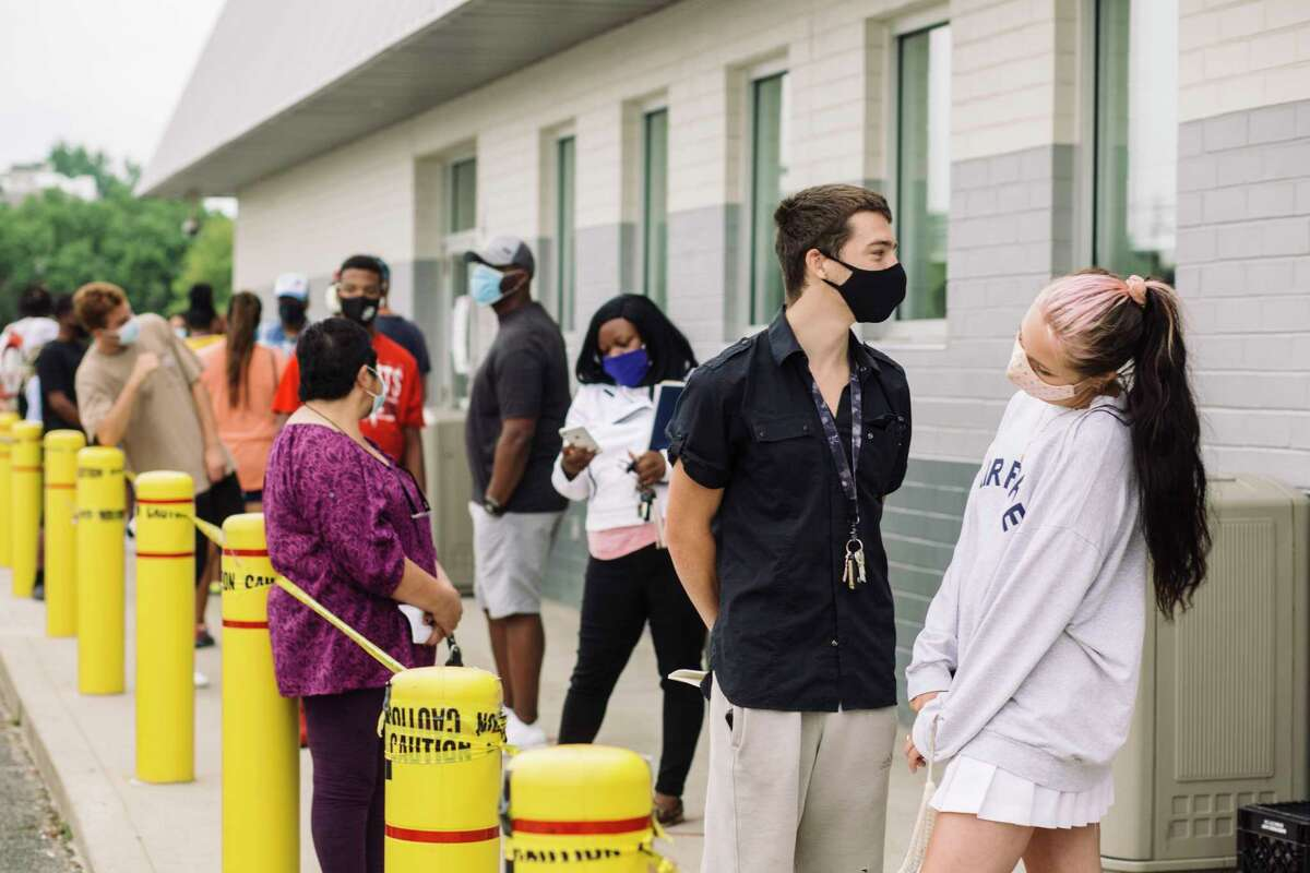Parker Smith and Chloe Lenox, front, stand at a distance from others outside an Ohio Bureau of Motor Vehicles office on June 30. The state is at risk of a new surge in cases.