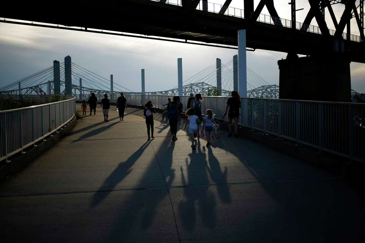 Pedestrians exercise on the Big Four walking bridge over the Ohio River in Louisville, Ky., on July 29. Kentucky's governor closed bars after being warned about the prospect of a dangerous surge in coronavirus cases.