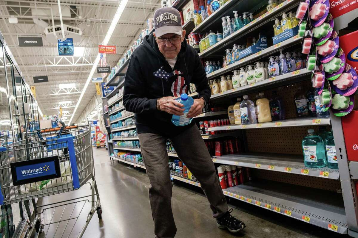 Dale Brown searches for hand sanitizer on empty shelves at Walmart in Fairfield, Calif., in February.