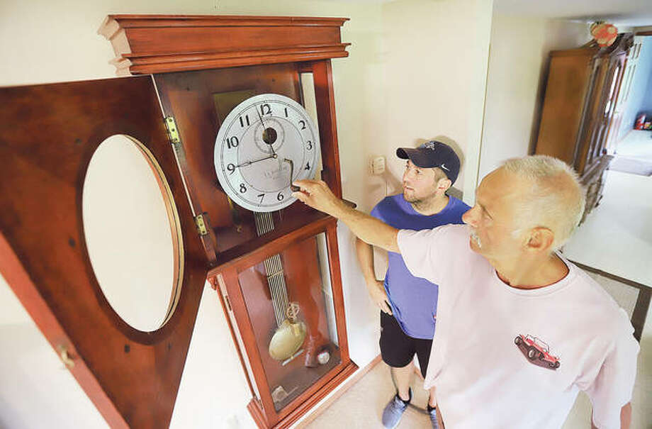 Kevin T. Goss, right, inserts the winding handle into the E.L. Barnard clock he is passing down to his son, Kevin W. Goss, left, at his rural Brighton home. This will be the third generation to treasure the 116-year-old clock. Photo: John Badman|The Telegraph