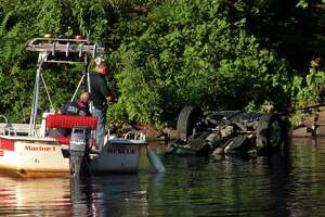 Officials investigate after a vehicle landed in the Housatonic River in Seymour on Friday.