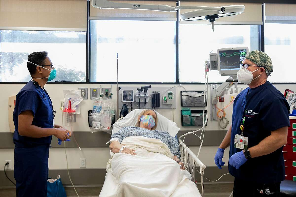 Nurse DJ (right, no last name given) wears a mask while checking in on a masked Los Gatos woman who declined to share her name who was admitted to the Emergency Department at Good Samaritan Hospital in San Jose, Calif. Friday, July 31, 2020 where doctors are currently treating twelve COVID-19 patients in various states of severity.