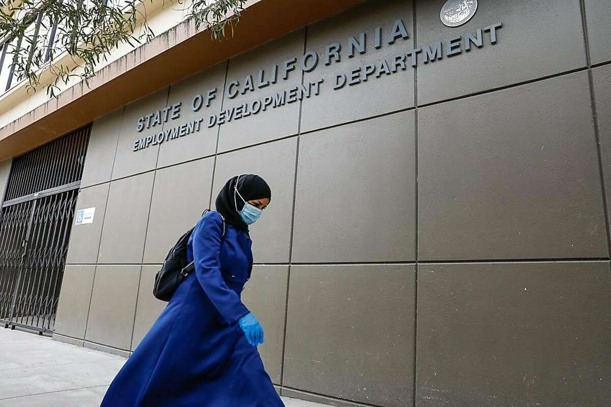 A woman walks by the Employment Development Department office on Monday, June 15, 2020 in San Francisco, California.