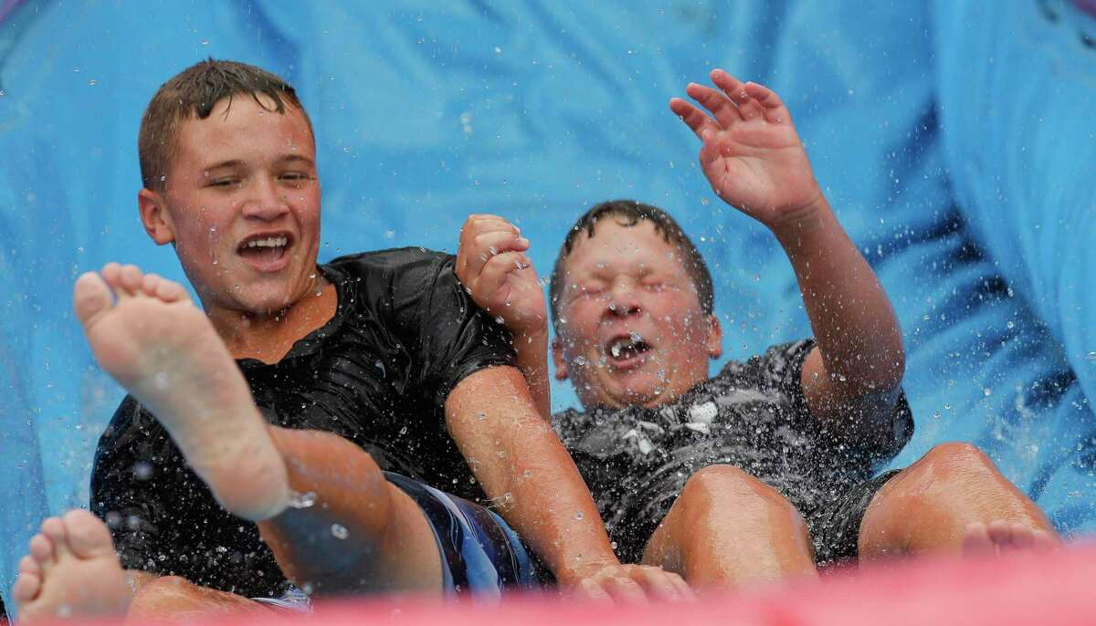 Dawson Patterson, left, slides down a waterslide with his brother, Joshua, during the Back 2 School Bash at Majestic Gym.