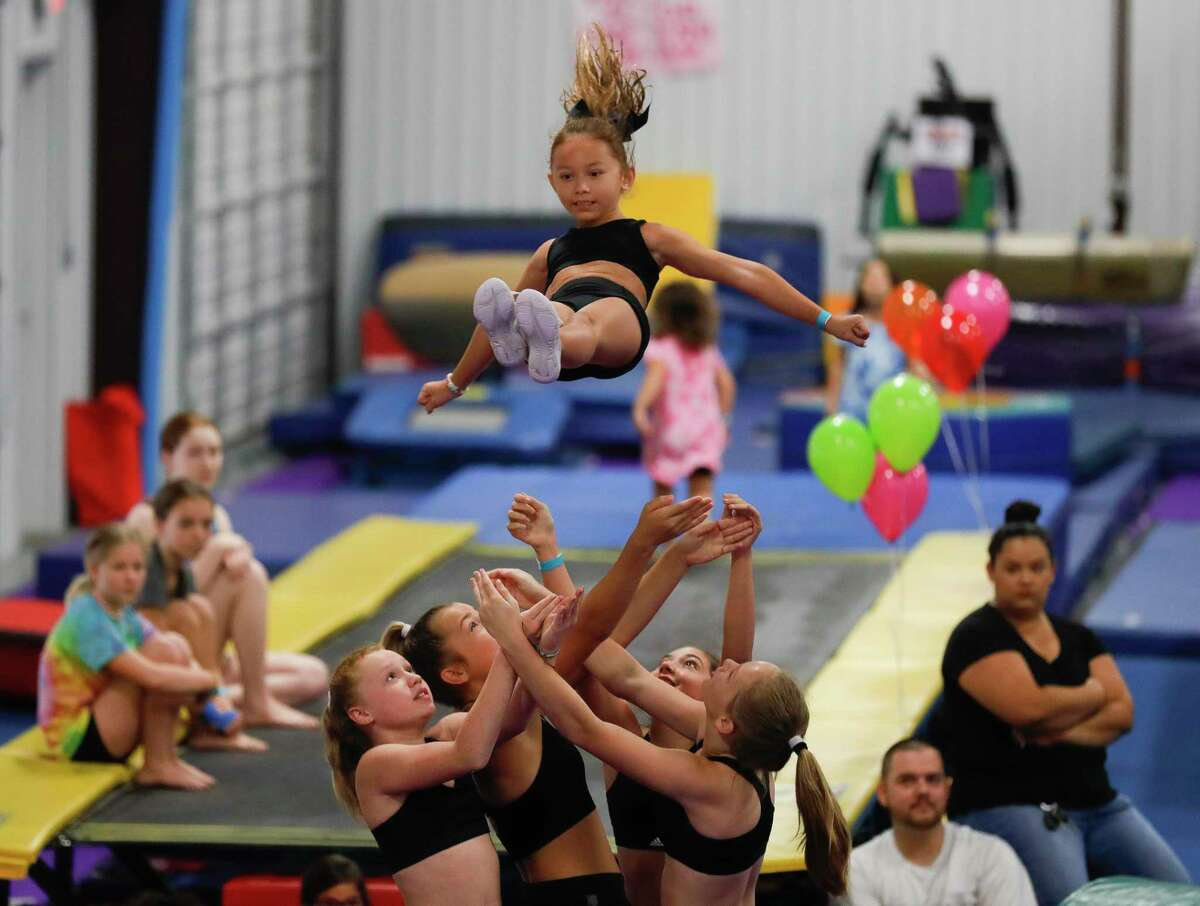 Linette Garris is caught by her cheerleader teammates as they perform during the Back 2 School Bash hosted by Majestic Gymnastics & Dance, Saturday, Aug. 1, 2020, in Willis. The free event featured performance by gymnastist, cheerleaders, food and games.