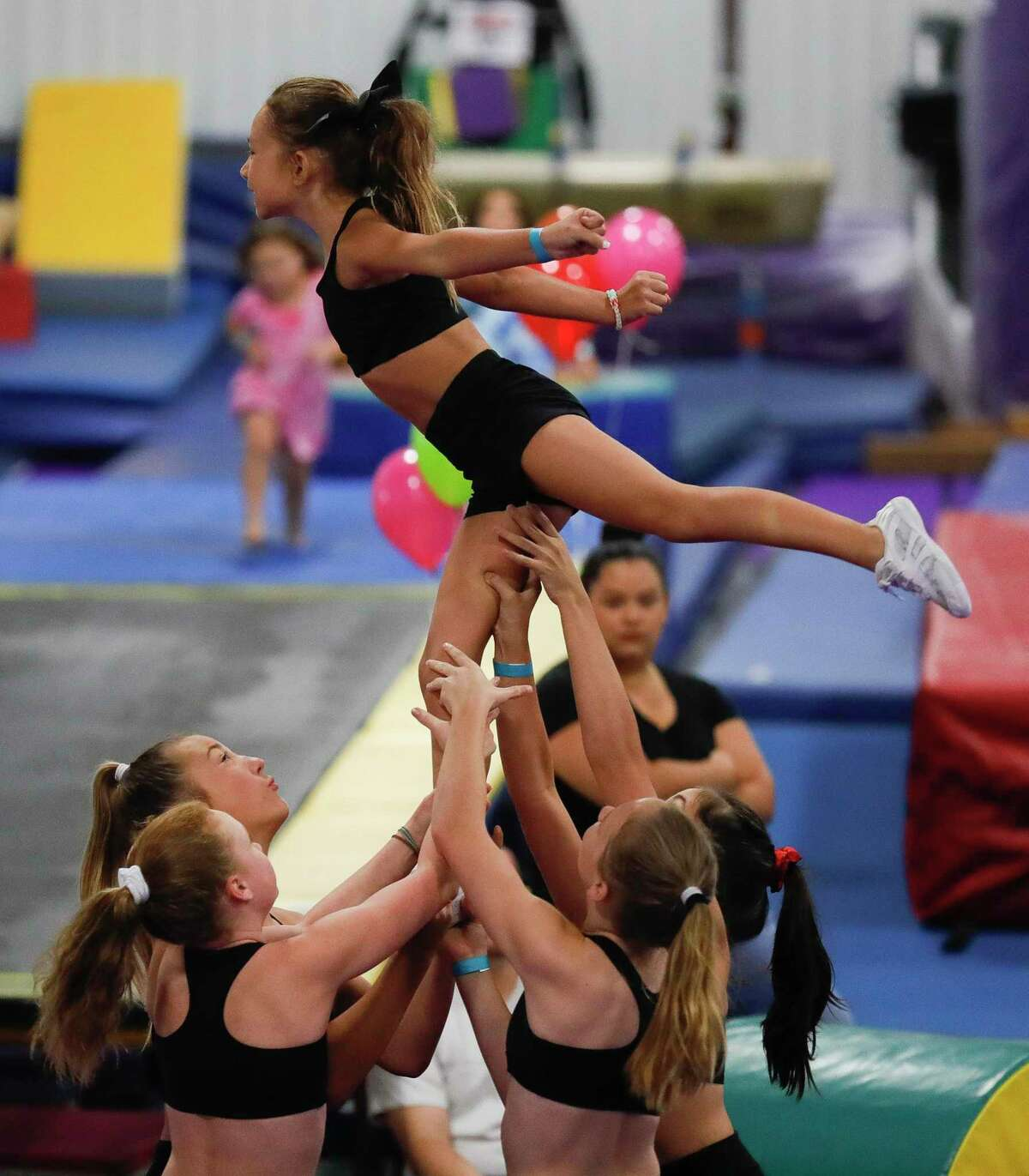 Linette Garris is held up by her cheerleader teammates as they perform during the Back 2 School Bash hosted by Majestic Gymnastics & Dance, Saturday, Aug. 1, 2020, in Willis. The free event featured performance by gymnastist, cheerleaders, food and games.