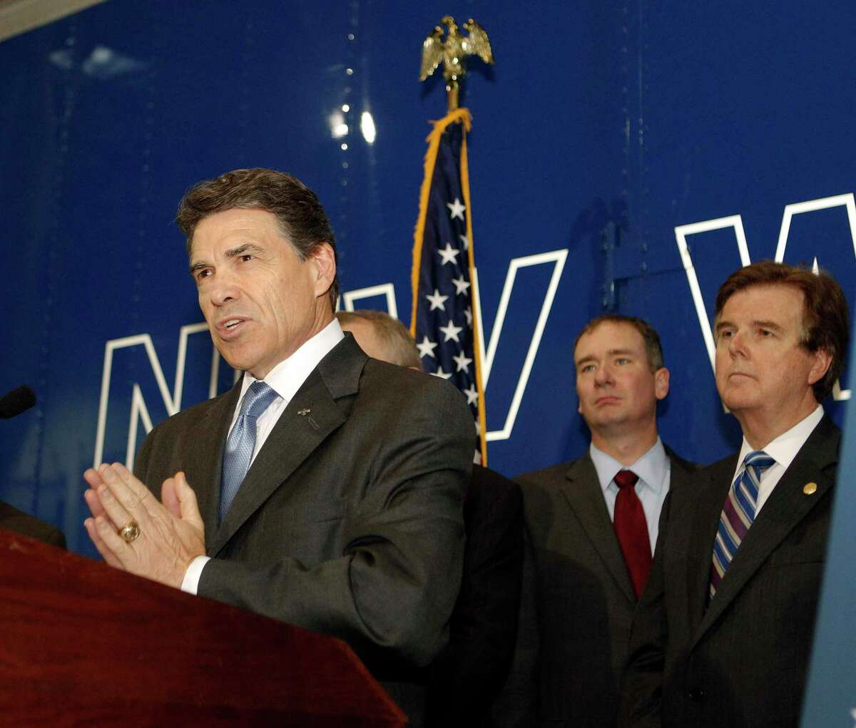Texas Governor Rick Perry left, as he announces the Texas Budget Compact, composed of five key principles during a press conference as Empower Texans President and CEO Michael Quinn Sullivan center, and Texas State Senator Dan Patrick look on at New World Van Lines Monday, April 16, 2012, in Houston.