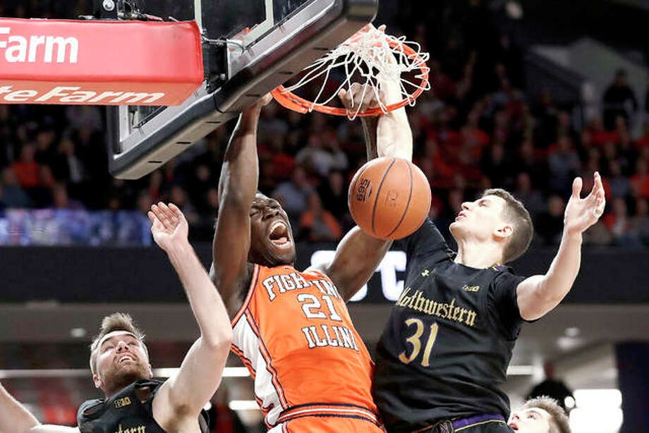 Illinois center Kofi Cockburn, center, has announced that he is returning for his sophomore season with the Illini, He had declared for the NBA Draft, but is withdrawing his name. Above, he dunks against Northwestern last season. Photo: AP Photo