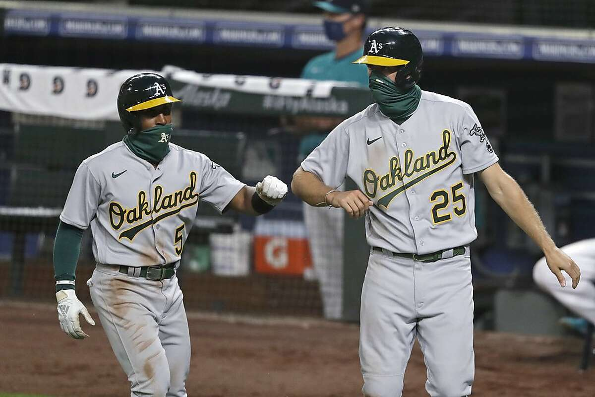 Oakland Athletics' Tony Kemp (5) and Stephen Piscotty (25) bump elbows in congratulations after both scored against the Seattle Mariners in the eighth inning of a baseball game during the Mariners home opener Friday, July 31, 2020, in Seattle. The Mariners won 5-3.(AP Photo/Elaine Thompson)