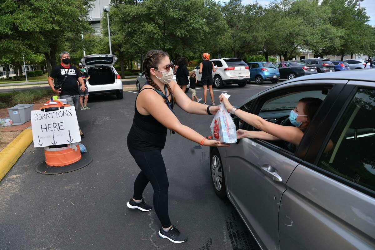 Corrine Lepere collects food donations during a Black Lives Matter National Day of Action car caravan and food drive that began at the ATT Center and traversed along Commerce Street to Monterey Park on the west side.