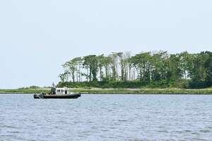 Emergency personnel search for a man who was swept off of a sandbar into the water while walking out to Charles Island at Silver Sands State Park in Milford, Conn. on Friday, July 21, 2017.