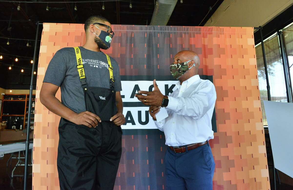 Marcus Baskerville of Weathered Souls Brewery (left) and Ivory Freeman of 100 Black Men talk after Baskerville and the brewery presented 100 Black Men with a check for $20,000.