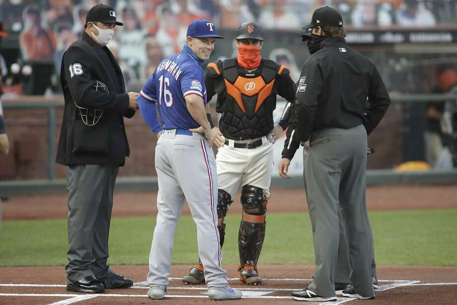 The Rangers' Scott Heineman (left) meets brother Tyler of the GIants at home plate, where they posed with the umpires before Saturday night's game in San Francisco. Photo: Ben Margot / Associated Press