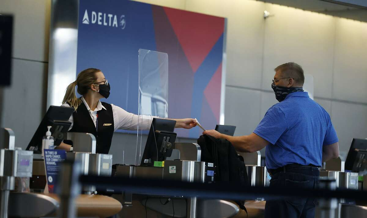 FILE - In this July 22, 2020 photo, a ticketing agent for Delta Airlines hands a boarding pass to a passenger as he checks in for a flight in the main terminal of Denver International Airport in Denver. Unions are gaining support in Congress for another $32 billion in federal aid to protect airline workers from layoffs for another six months. Still, it's too early to say how the issue will turn out. (AP Photo/David Zalubowski, File)