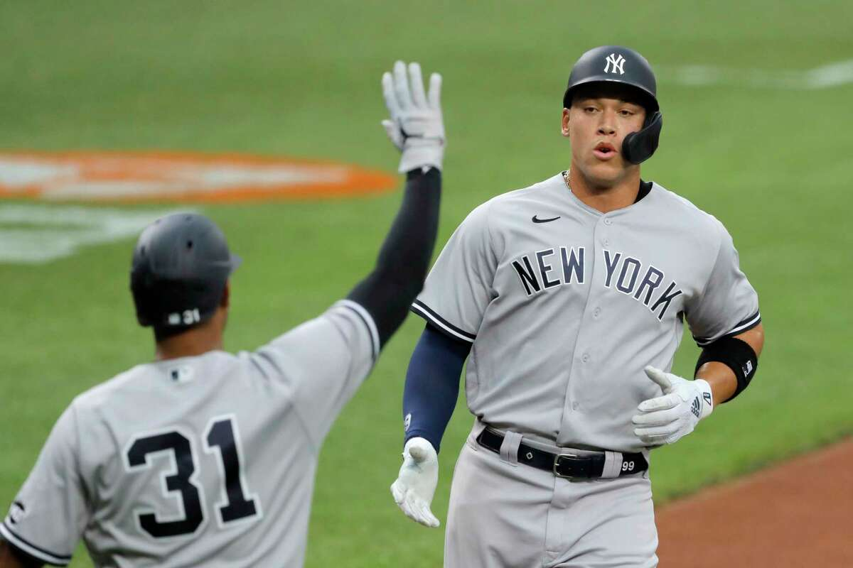 New York Yankees' Aaron Judge, right, is greeted at home by Aaron Hicks (31) after scoring on a single by Giancarlo Stanton off Baltimore Orioles starting pitcher John Means during the first inning of a baseball game, Thursday, July 30, 2020, in Baltimore. (AP Photo/Julio Cortez)