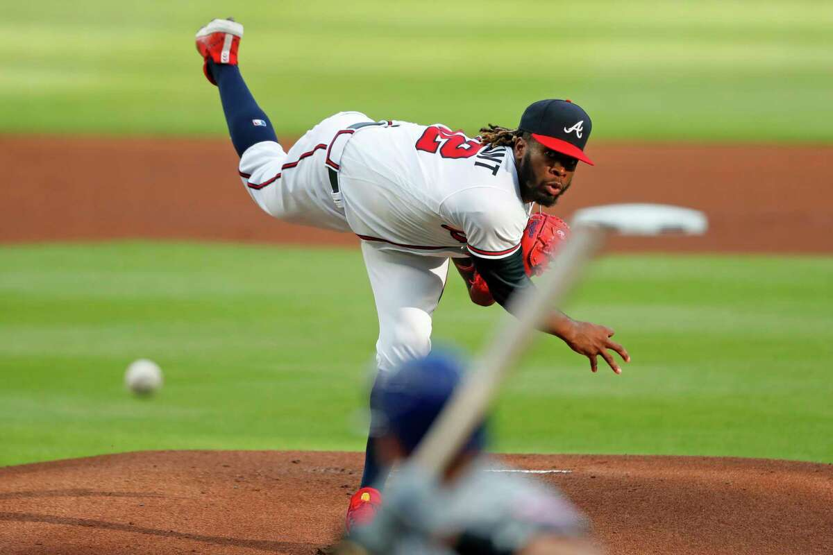 Atlanta Braves relief pitcher Touki Toussaint, top, delivers to New York Mets' Jeff McNeil in the first inning of a baseball game Saturday, Aug. 1, 2020, in Atlanta. (AP Photo/John Bazemore)