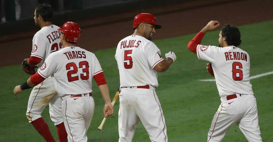 Albert Pujols #5, Anthony Rendon #6 , Matt Thaiss #23 of the Los Angeles Angels, and David Fletcher #22 of the Los Angeles Angels celebrate defeating the Houston Astros 5-4 in the tenth inning of a game at Angel Stadium of Anaheim on August 01, 2020 in Anaheim, California. (Photo by Sean M. Haffey/Getty Images) Photo: Sean M. Haffey/Getty Images / 2020 Getty Images