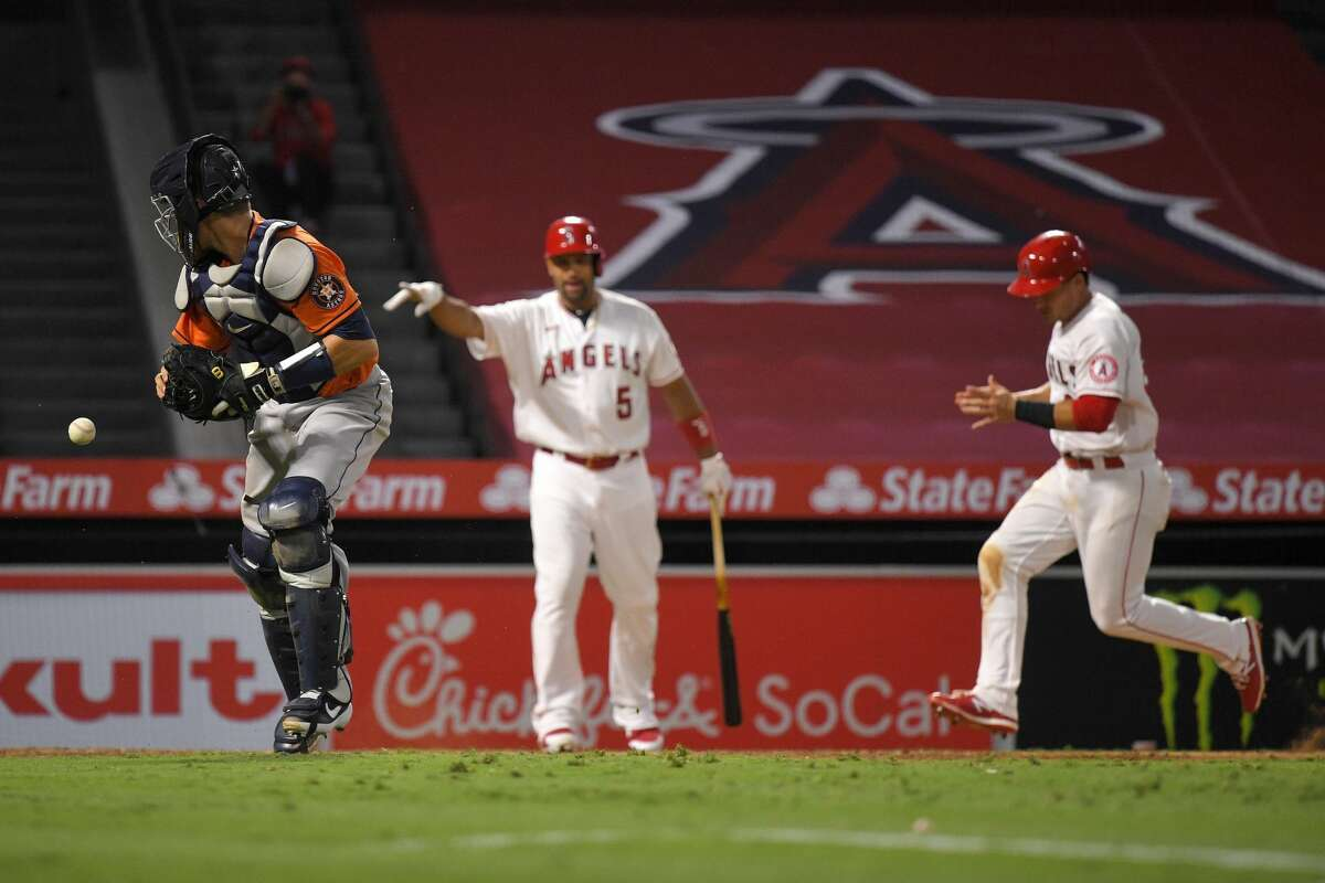Los Angeles Angels' Matt Thaiss, right, scores the winning run on a sacrifice fly by Michael Hermosillo as Houston Astros catcher Dustin Garneau, left, loses the ball and Albert Pujols points during the 10th inning of a baseball game Saturday, Aug. 1, 2020, in Anaheim, Calif. (AP Photo/Mark J. Terrill)