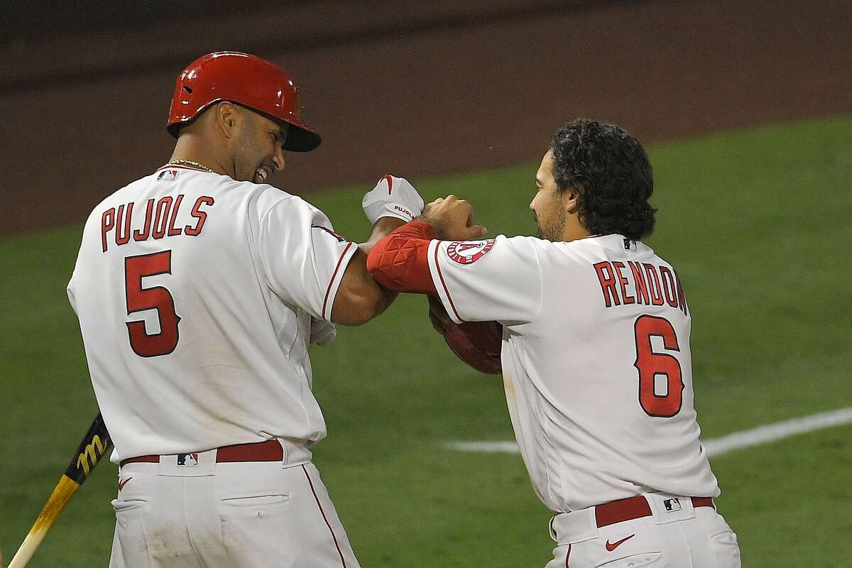 Albert Pujols (left) and Anthony Rendon celebrate after Matt Thaiss scored the game-winning run.