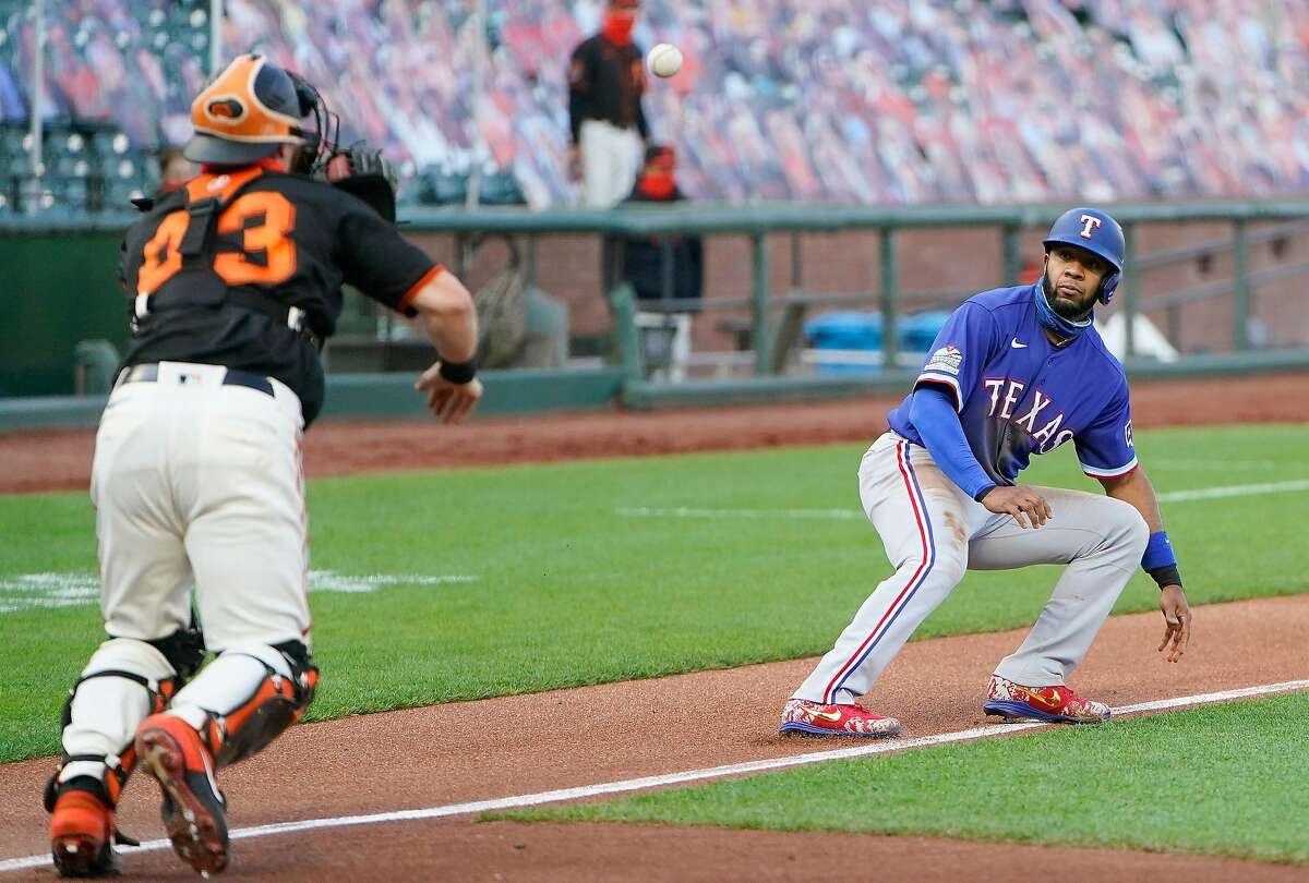 SAN FRANCISCO, CALIFORNIA - AUGUST 01: Elvis Andrus #1 of the Texas Rangers gets caught in a rundown chased back towards third base by Tyler Heineman #43 of the San Francisco Giants in the top of the first inning at Oracle Park on August 01, 2020 in San Francisco, California. Andrus was safe at third base on the play and later scored. (Photo by Thearon W. Henderson/Getty Images)