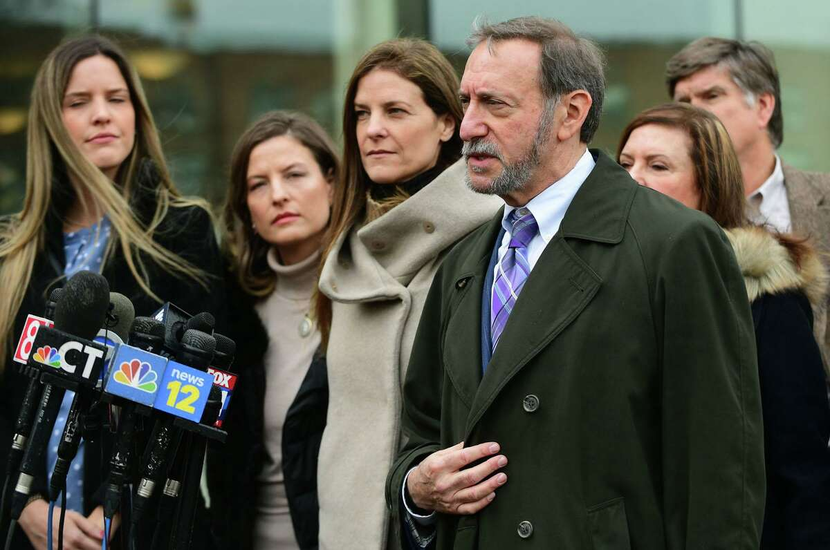 Defense attorney Jon Schoenhorn speaks to the media outside the Stamford courthouse in February as his client, Michelle Troconis, center, stands with her family.