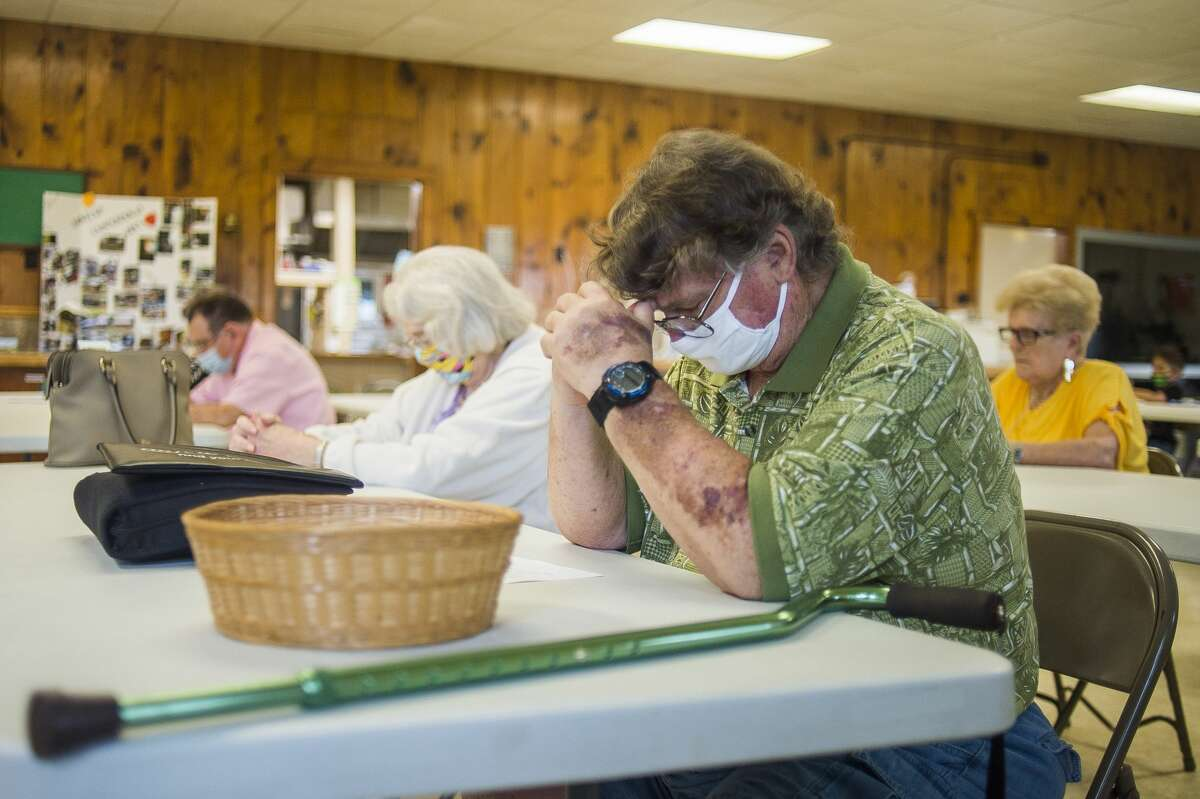 John Walker bows his head in prayer as congregants of Sanford Community of Christ Church gather for service Sunday, Aug. 2, 2020 at Community of Christ Campground, a temporary location while renovation continues on the church's main building in downtown Sanford. (Katy Kildee/kkildee@mdn.net)