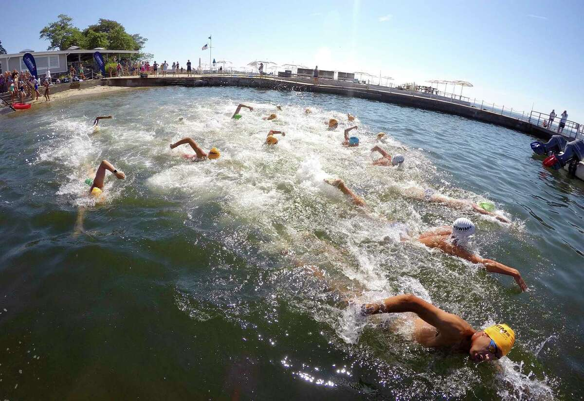 Swimmers head out from the Rocky Point Club in Old Greenwich, Connecticut on August 1, 2020 tp participate in the