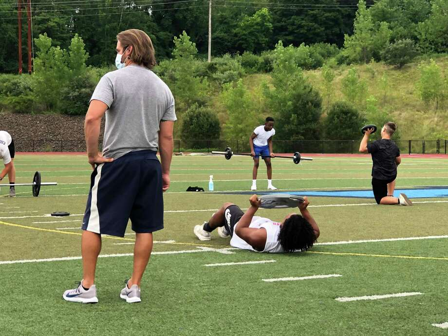 Middletown High football players go through their paces during conditioning drills at the school last week while assistant coach Jason Coleman, left, looks on. Photo: Paul Augeri / For Hearst Connecticut Media