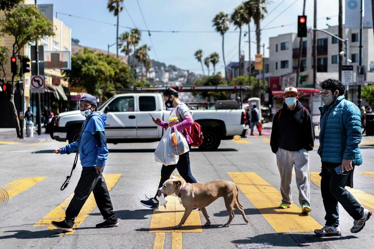 People and a pooch walk on Mission Street in San Francisco on July 13, 2020.