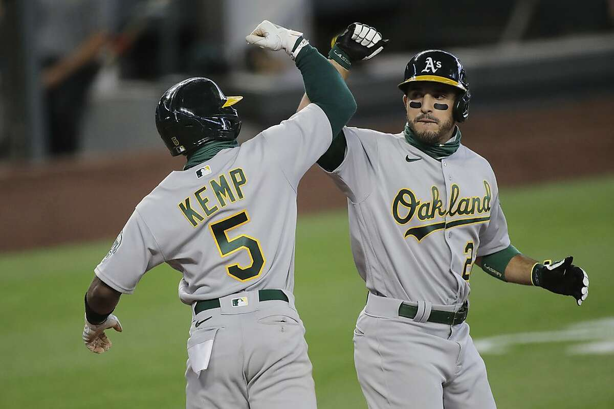 Oakland Athletics' Ramon Laureano, right, is greeted by Tony Kemp (5) after Laureano hit a three run home run to score Kemp and Marcus Semien during the fifth inning of a baseball game against the Seattle Mariners, Sunday, Aug. 2, 2020, in Seattle. (AP Photo/Ted S. Warren)