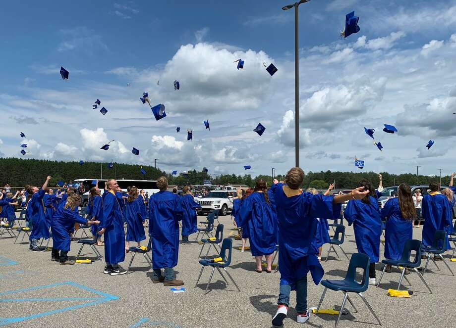 Evart High School held its graduation ceremony at 2 p.m., Sunday, Aug. 1, in the Evart High School parking lot.Parents remained in their vehicles throughout the duration of the ceremony. Graduates, who were seated in front of the stage, wore face coverings, many wearing blue and gold masks with the class of 2020 logo. Photo: Pioneer Photo/Cathie Crew