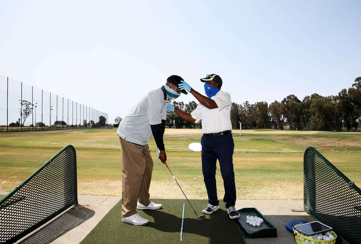 """Chad Burr, 38, of San Leandro, left, receives a golf lesson from Winslow """"Woody"""" Woodard, 68, Corica Park Golf Course on Saturday, August 1, 2020, in Alameda, Calif. Woodard is a longtime instructor at Corica Park, where he has been giving lessons for 40 years."""