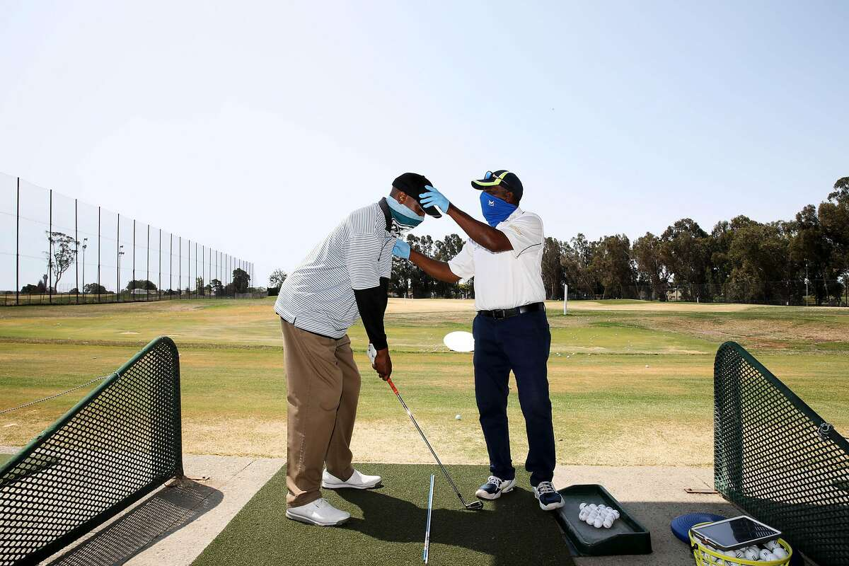 "Chad Burr, 38, of San Leandro, left, receives a golf lesson from Winslow ""Woody"" Woodard, 68, Corica Park Golf Course on Saturday, August 1, 2020, in Alameda, Calif. Woodard is a longtime instructor at Corica Park, where he has been giving lessons for 40 years."