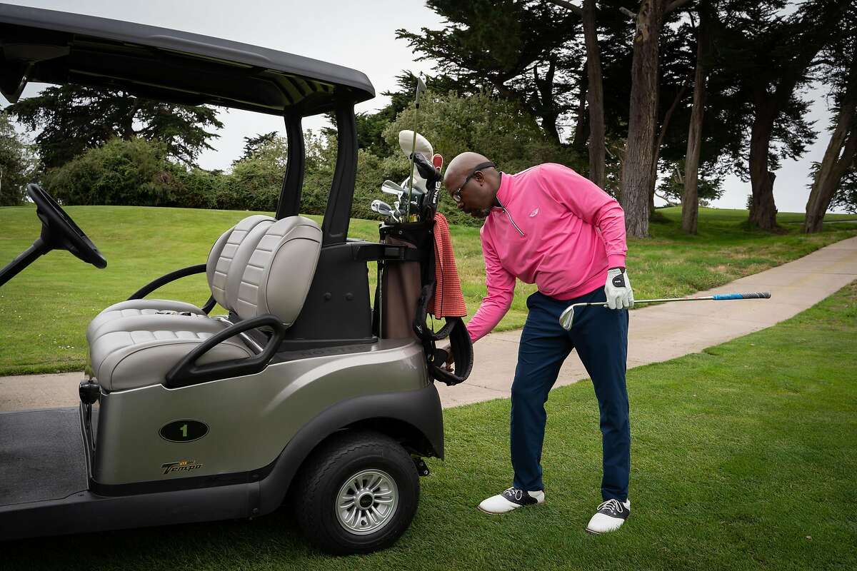 Willie Toney, 54, Assistant Head Golf Pro, grabs equipment from a golf cart at Olympic Club in San Francisco, Calif., on Thursday, July 30, 2020.