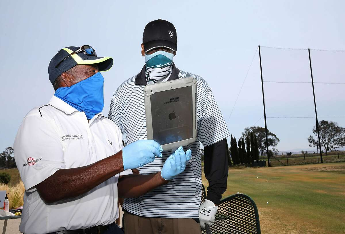 """Winslow """"Woody"""" Woodard, 68, left, shows an image of student Chad Burr's golf swing to him during a golf lesson at Corica Park Golf Course on Saturday, August 1, 2020, in Alameda, Calif. Woodard is a longtime instructor at Corica Park, where he has been giving lessons for 40 years."""