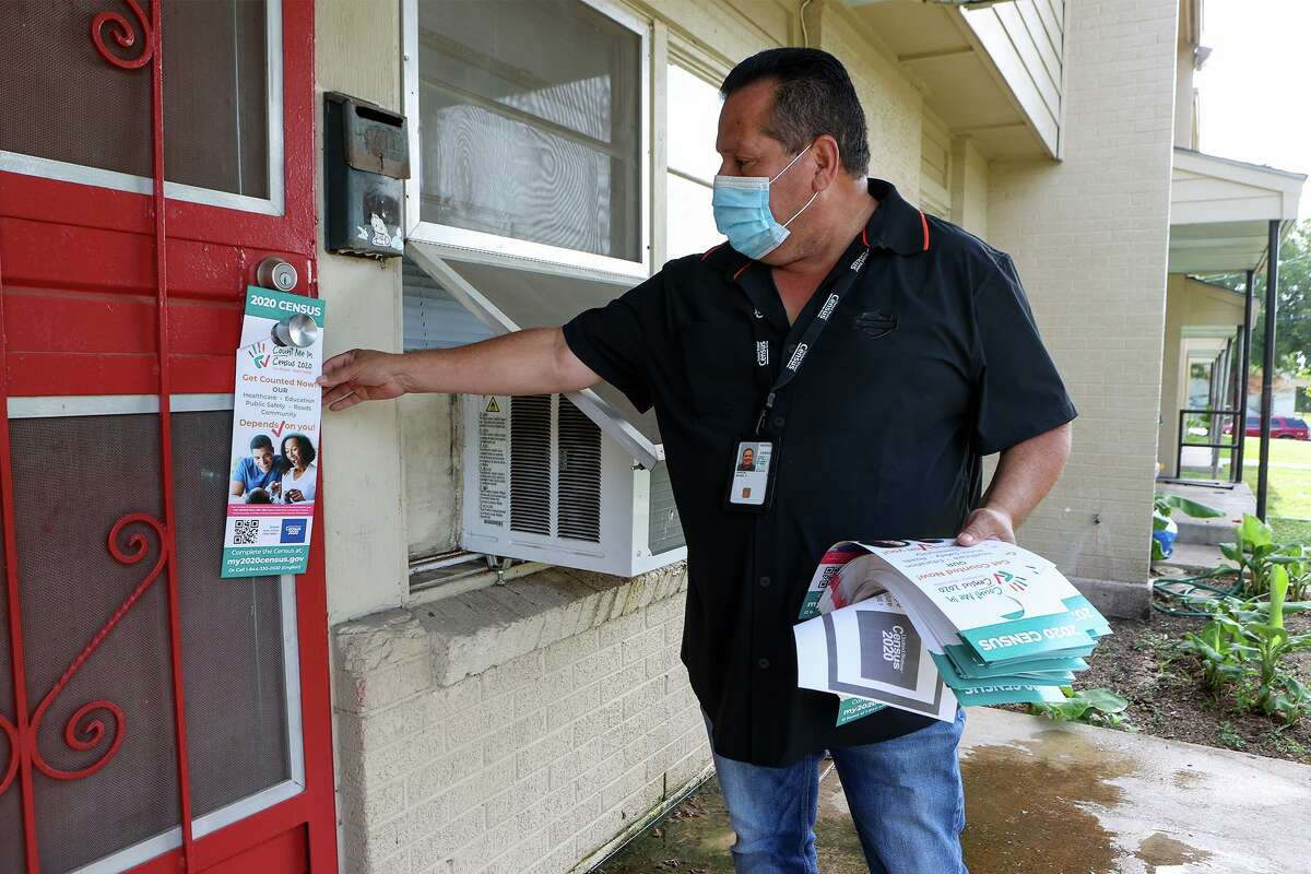 Manny Garcia, a recruit assistant with the U.S. Census Bureau, hangs a flyer encouraging residents to fill out their 2020 census forms earlier this month. An incomplete count will cost Texas in representation and federal funding.