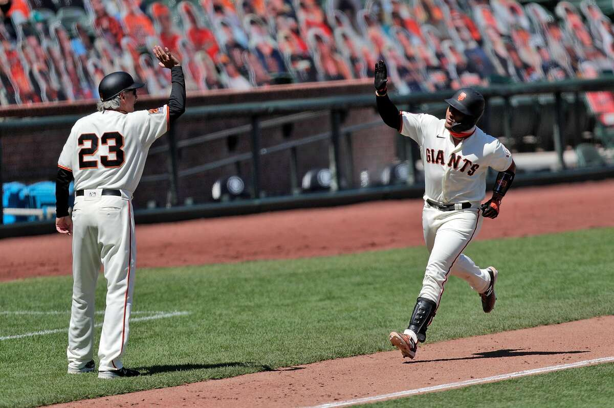 Chadwick Tromp (14) gestures to third base coach Ron Wotus as he rounds the bases after hitting his two-run homerun in the sixth inning, his first in the majors, as the San Francisco Giants played the Texas Rangers at the Oracle Park in San Francisco, Calif., on Sunday, August 2, 2020.