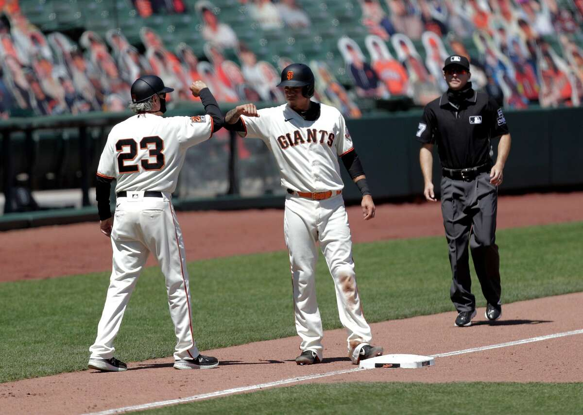 Wilmer Flores (41) bumps elbows with third base coach Ron Wotus after reaching third on an rbi fielder's choice hit by Mike Yastrzemski (5) that scored Brandon Crawford (35) in the fifth inning as the San Francisco Giants played the Texas Rangers at the Oracle Park in San Francisco, Calif., on Sunday, August 2, 2020.