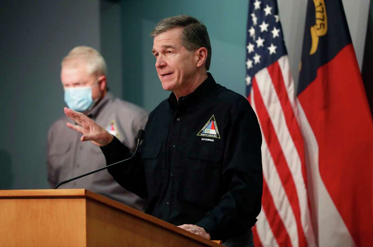North Carolina Gov. Roy Cooper answers a question while giving an update on North Carolina's preparations for Tropical Storm Isaias during a press conference in the Emergency Operations Center in Raleigh, N.C., Sunday, Aug. 2, 2020. (Ethan Hyman/The News & Observer via AP)