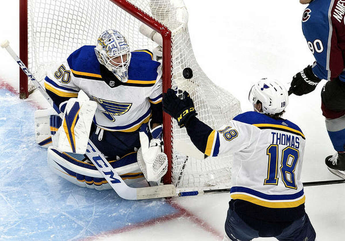 Blues goalie Jordan Binnington (50) makes a save as Robert Thomas (18) reaches for the rebound during the first period against the Colorado Avalanche in round-robin NHL hockey playoff game Sunday in Edmonton, Alberta.