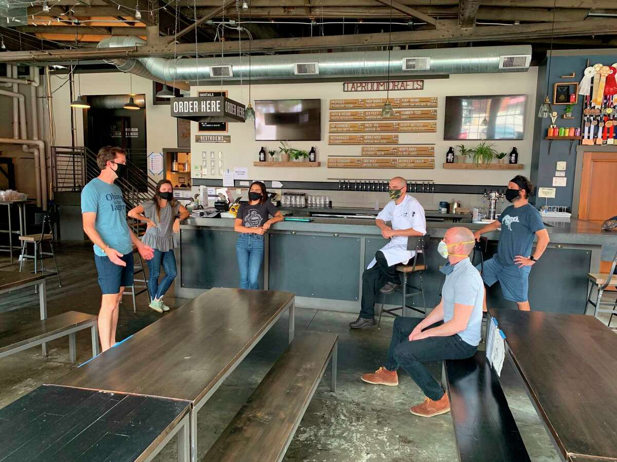 In a July 2020 photo provided by Wolf's Ridge Brewing, owner Bob Szuter, employees Allison Randolph and Alicia Herrmann, sous chef Andy Zamagias, general manager Corey Schlosser and employee Andy Powell, from left, gather inside the restaurant's tap room in Columbus, Ohio. Szuter says hea€™s trying to figure out new ways to bring in revenue, focusing more on the brewery side of the business until ita€™s safe to have a full dining room. (Charlie Wilkerson/Wolf's Ridge Brewing via AP)